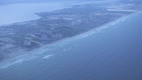 Aerial view on city on sea shore. View from window flying airplane over modern city on sea coast. Landscape from above stock video