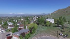 Aerial view of a city in a wide valley with snowcapped mountains in the distance. Starting with a view of the foothills and then a city in a vast valley with a stock video