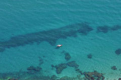 Aerial view of clear blue water and yellow boat Stock Photo