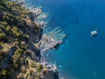 Aerial view of a cliff overlooking the sea and a moored catamaran, boat. Corsica. Coastline. France Stock Photography