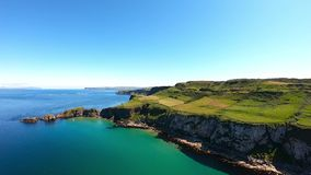 Aerial view of Cliffs and turquoise Atlantic Ocean water, Carrick a Rede Rope Bridge in Northern Ireland.  stock video footage