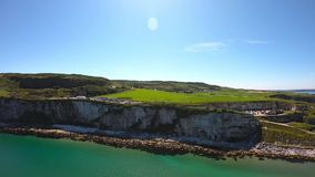 Aerial view of Cliffs and turquoise Atlantic Ocean water, Carrick a Rede Rope Bridge in Northern Ireland.  stock footage