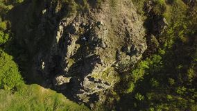 Aerial view of climber solo free climbing on cliffs alone. Man climb the rock without safety harness and ropes. Male. Aerial view of climber solo free climbing stock video