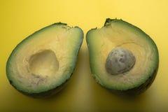Aerial view closeup fresh guacamole half on yellow cutting board Stock Image