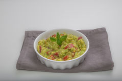 Aerial view closeup white bowl with spicy guacamole dip. Top view of fresh ingredients for guacamole, avocado tomatoes onion garlic pepper lemon juice Stock Images
