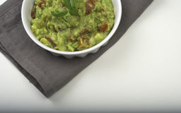 Aerial view closeup white bowl with spicy guacamole dip. Top view of fresh ingredients for guacamole, avocado tomatoes onion garlic pepper lemon juice on grey Royalty Free Stock Photos