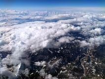 Aerial view of cloud covered mountain landscape with snow visible on green hills and mountains with the curvature of the earth. Visible on the horizon and blue royalty free stock images