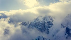 Aerial view of clouds circling around mountain ridge. Royalty Free Stock Image