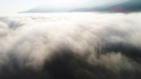 Aerial view of clouds and landscape under them. Shot. Top view of the clouds under the sky. Under the clouds shot from a