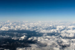 Aerial View of a Cloudscape and mountains below. Royalty Free Stock Image