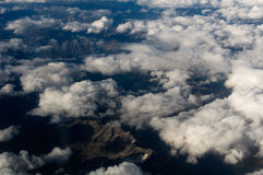 Aerial View of a Cloudscape and mountains below. Royalty Free Stock Photos