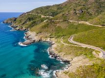 Aerial view of the coast of Corsica, winding roads and coves with crystalline sea. France. Aerial view of the coast of Corsica, winding roads and coves with Royalty Free Stock Image