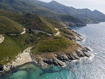 Aerial view of the coast of Corsica, winding roads and coves with crystalline sea. France. Aerial view of the coast of Corsica, winding roads and coves with Royalty Free Stock Photo
