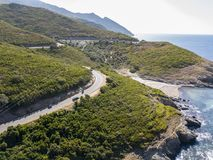 Aerial view of the coast of Corsica, winding roads and coves with crystalline sea. France. Aerial view of the coast of Corsica, winding roads and coves with Stock Photo