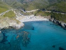 Aerial view of the coast of Corsica, winding roads and coves with crystalline sea. Gulf of Aliso. France. Aerial view of the coast of Corsica, winding roads and Stock Photography
