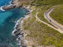 Aerial view of the coast of Corsica, winding roads and coves. Motorcyclists parked on the edge of a road. France Stock Photo
