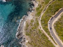 Aerial view of the coast of Corsica, winding roads and coves. Motorcyclists parked on the edge of a road. France Royalty Free Stock Photos