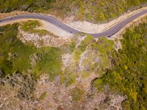 Aerial view of the coast of Corsica, winding roads. Cyclists running on a road. France. Aerial view of the coast of Corsica, winding roads. Cyclists running on a royalty free stock photography