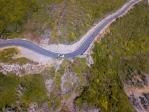 Aerial view of the coast of Corsica, winding roads. Cyclists running on a road. France. Aerial view of the coast of Corsica, winding roads. Cyclists running on a stock photography