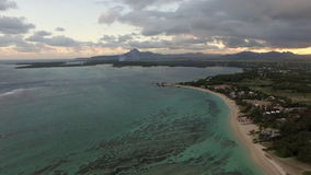 Aerial view of coast line of Mauritius Island. Aerial view of rugged coast line of Mauritius Island, water laves sand strand, cloudy sky, forests and hills stock footage
