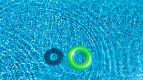 Aerial view of colorful inflatable ring donut toy in swimming pool water from above Royalty Free Stock Photography