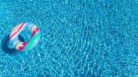 Aerial view of colorful inflatable ring donut toy in swimming pool water from above, family vacation concept. Background Royalty Free Stock Photos