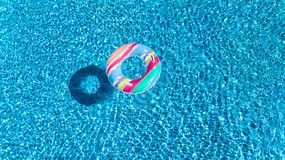 Aerial view of colorful inflatable ring donut toy in swimming pool water from above, family vacation concept. Background Stock Photo