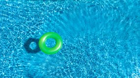 Aerial view of colorful inflatable ring donut toy in swimming pool water from above, family vacation concept. Background Stock Images