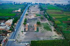 Aerial view of the Colossi of Memnon, Two massive stone statues of the�Pharaoh�Amenhotep III. Aerial view of the Colossi of Memnon, Two massive stone statues Royalty Free Stock Images