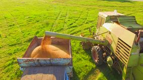 AERIAL VIEW. Combine Harvester In Action On Wheat. AERIAL VIEW. Slow motion. Harvester produces loading mown crops. Through deflector grain gets into a truck stock footage