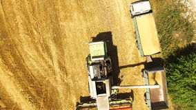 Aerial view of a combine harvester pouring wheat on a truck in a field in 4k.  stock footage