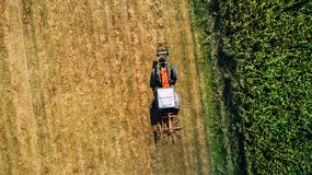 Aerial view of combine harvester, tractor on hay field. Agriculture and harvesting. Wheat production . stock images