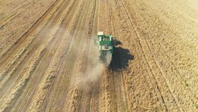 Aerial view of combine harvester on wheat field. Smooth approach to the object. stock video footage