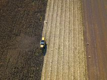 Aerial view of combine harvesting on corn field. Aerial view of yellow combine harvesting on corn field Royalty Free Stock Images