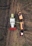 Aerial view of combine pouring harvested corn grains into traile Stock Photos