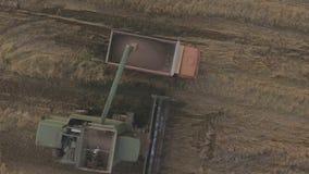 Aerial view combine unloads grain in the truck. stock footage