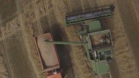 Aerial view combine unloads grain in the truck. stock video footage