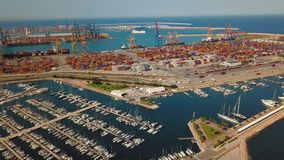 Aerial view of the commercial port and the marina with yachts in Valencia. Container terminal and ship during loading. Aerial view of the commercial port and stock video