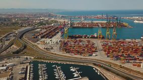 Aerial view of the commercial port and the marina with yachts in Valencia. Container terminal and ship during loading. Aerial view of the commercial port and stock footage