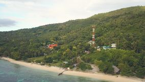 Aerial view communications tower and building on green highlands on sea shore. Drone view houses and buildings on green.  stock video