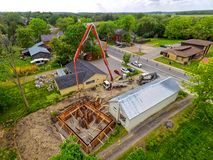 Aerial View of a Concrete Foundation Being Poured. Aerial View of a Concrete Pump Truck Pouring a Foundation for an Addition on an Old Building royalty free stock images