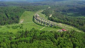 Arched railroad bridge in green countryside