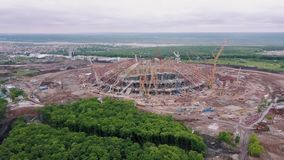 Aerial view on construction area of large modern sporting arena, huge building cranes. Are standing around stock footage