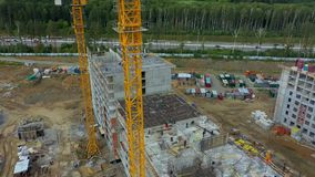 An aerial view of construction site near the green forest. A big residential complex is under the construction with