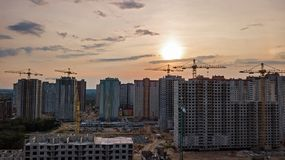 Aerial view of construction site of residential area buildings with cranes at sunset from above, urban skyline Royalty Free Stock Images