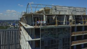 Aerial View Of Construction Site With Team Of Builders On Roof Discussing Plan Of Project. Drone Shot stock footage