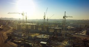 Aerial view of the construction site and yellow cranes. new apartment building in progress.  royalty free stock photos