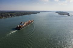 Aerial view of a container ship going upstream in the St. Lawrence River near the port of Montreal in Canada royalty free stock photography