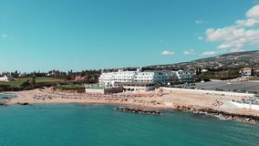 Aerial view of coral bay sandy beach in cyprus paphos with blue water and waves on sunny windy day. Drone flying over clean sandy stock footage