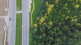 Aerial view at the country highway passing near forest in evergreen northern forests. Clip. Top view of the motorway. Near the forest royalty free stock images